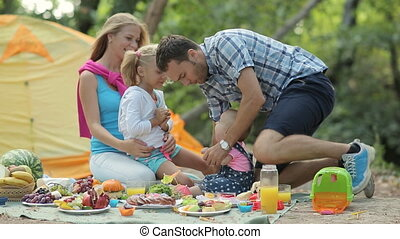 Parents with two children on a picnic in the woods,daughters...