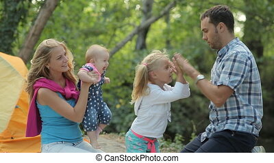 Happy family on picnic in the woods, dad and daughter playing patty-cake