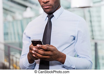 Businessman typing message Cropped image of young African...