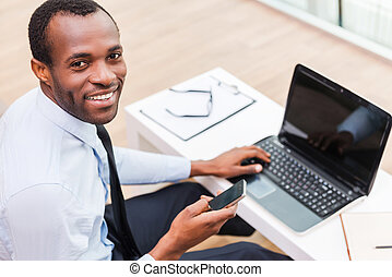 Working with smile Top view of young African man in...