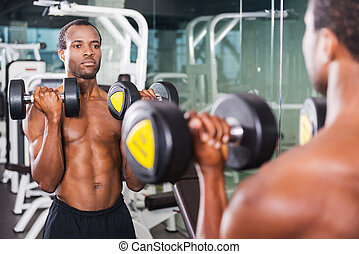 Weightlifting. Handsome young African man training with dumbbells in gym while standing against mirror