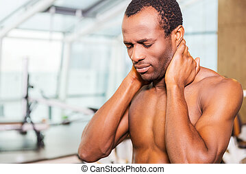 Feeling neckache after workout. Frustrated young African man...