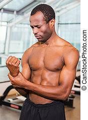 Feeling pain after workout. Frustrated African man touching his arm and expressing negativity while standing in gym