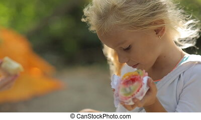Little blond girl eating a beautiful cake with fruit on the...