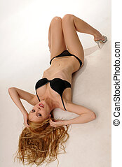 Blonde - Beautiful blonde in black lingerie lying on a white...