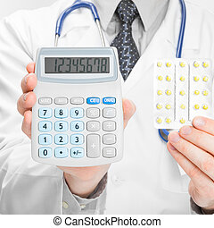 Doctor holdling calculator and pills in his hands - medical...