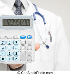 Doctor holding in his hand calculator - health care concept