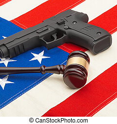 Wooden judge gavel and gun over USA flag - self-defense law...
