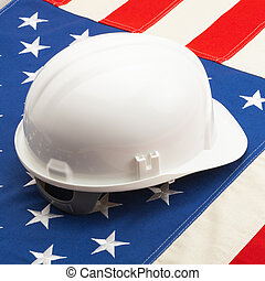 White color construction helmet laying over US flag -...
