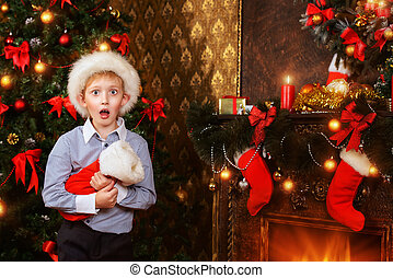 surprised boy - Cute seven year old boy stands with a gift...