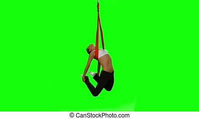 Young woman making antigravity yoga exercises with red...