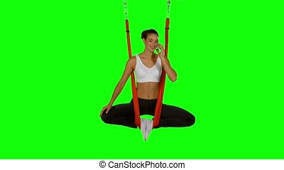 Young woman making antigravity yoga exercises with red hammock on a green screen. Talking on the phone
