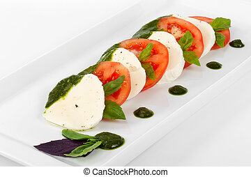 Tomato and mozzarella slices decorated with basil leaves on a pl