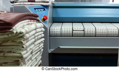 Laundry worker puts ironed towels in pile - View of laundry...