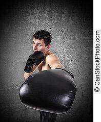 boxer strikes - Young boxer strikes on a gray background