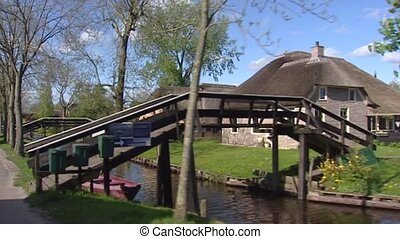 Vehicle shot Giethoorn village, with houses built on little...