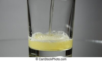 Beer is poured into a glass rotating