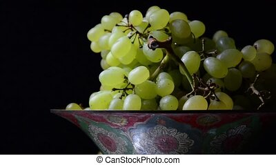 White grapes on an old painted bowl on a black background...