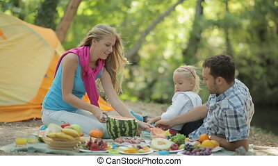 Happy family consisting of parents and little daughter at a picnic in the woods