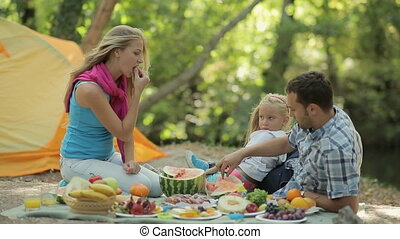 Happy family consisting of parents and little daughter eating watermelon at the picnic in the forest
