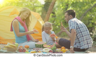 Parents with a beautiful little girl eating watermelon at the picnic in the forest
