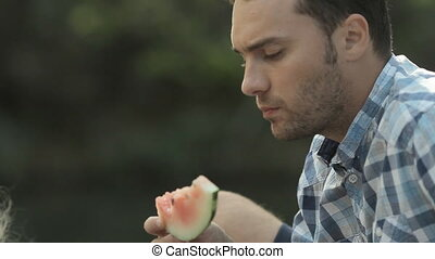 Family of three eating watermelon in nature with gusto -...
