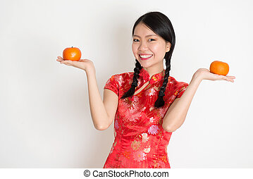 Asian chinese girl holding tangerine orange - Portrait of...