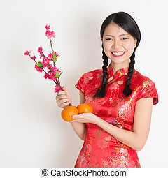 Asian chinese girl holding tangerine and plum blossom -...