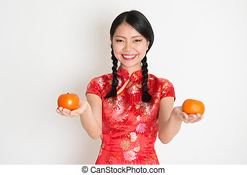 Asian chinese girl holding tangerine - Portrait of Asian...