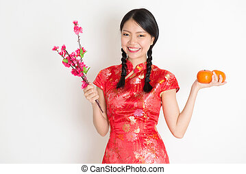 Asian chinese girl holding tangerine orange and plum blossom...