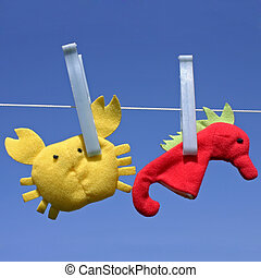 Toys hanging on clothesline - Two funny sea creature toys...