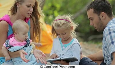 Little girl studying tablet on a picnic with her family in...