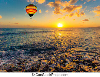 Hot air balloon over the sea at sunset