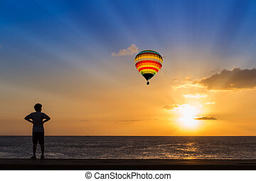 Silhouette man and hot air balloon at sunset over ocean