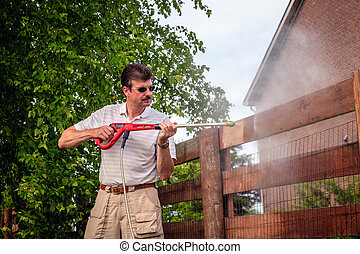 Fence power washing - A man is cleaning wooden fence with...