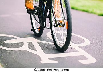 People cycling bike commuting - City bike sign on asphalt...