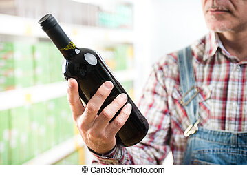 Farmer buying wine at supermarket - Farmer holding a wine...