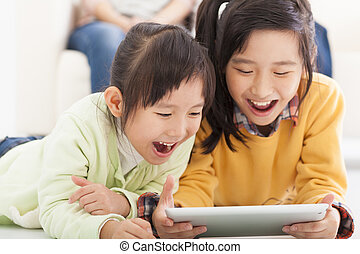 happy asian little girls using tablet computer
