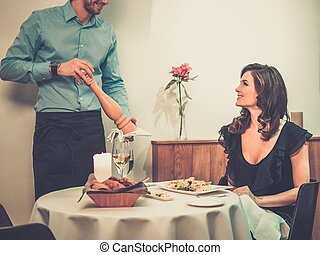 Beautiful young lady and waiter in restaurant