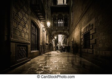 People walking at Carrer del Bisbe in Barri Gotic, Barcelona...