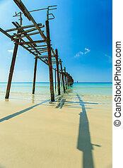 Long wood bridge on the beach with blue sky