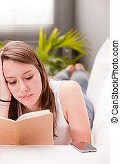 lying girl studying on a sofa
