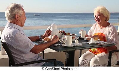 Breakfast at the hotel - Happy senior couple enjoying their...