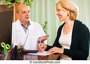 Male doctor talking with smiling mature patient in clinic...