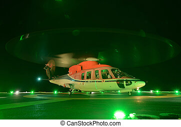 The helicopter night landing on offshore oil rig platform