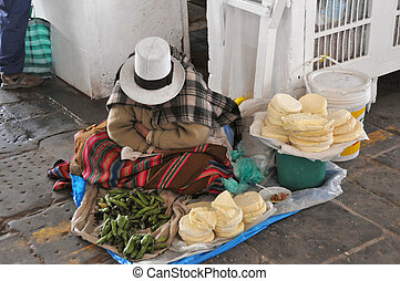 Peruvian woman selling cheese and vegetables in a market in...