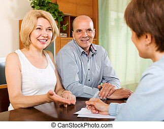 Mature couple with insurance agent - Smiling elderly couple...
