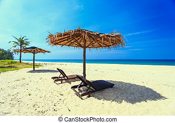 Sun umbrella and sunbed with tourist on the white beach in blue