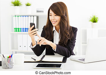 happy business woman using the smart phone in office