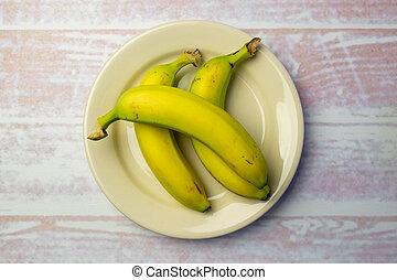 White round plate with three bananas